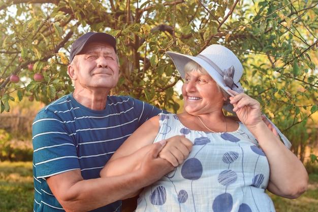 Tir en plein air authentique d'un couple vieillissant s'amusant dans le jardin et béni d'amour