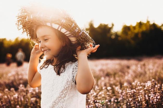 Tir en plein air d'un enfant doux jouant dans un champ de fleurs. belle petite fille qui court et s'amuse à rire avec une couronne de fleurs sur la tête.