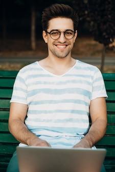 Tir en plein air d'un homme vlogger regardant la caméra en souriant. influenceur masculin assis sur un banc avec un ordinateur portable sur ses jambes.