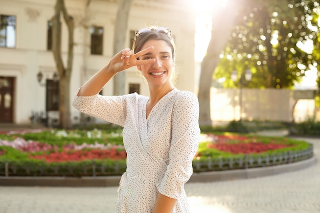 Tir en plein air de jeune femme brune joyeuse en robe à pois blanc souriant largement et levant la main avec le geste de la victoire, debout sur l'environnement urbain