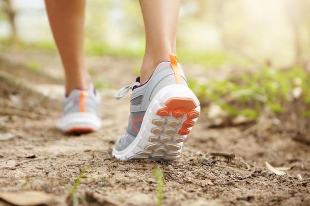 Tir recadré arrière de jambes athlétiques de femme jogger portant des chaussures de course roses pendant l'exercice de jogging à l'extérieur.