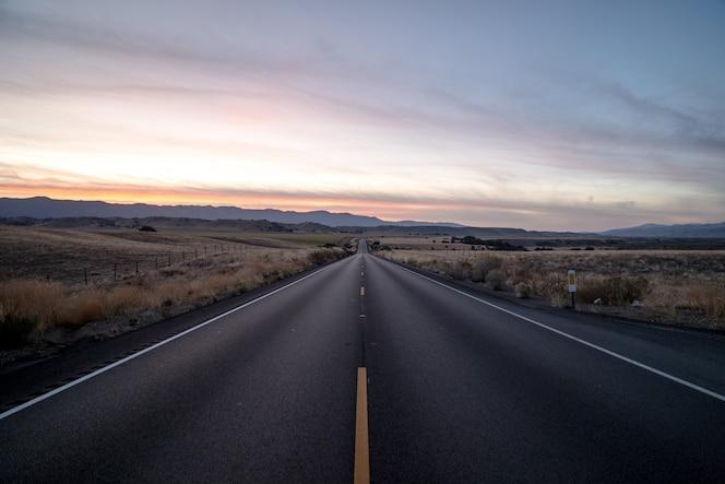 Tir d'une route routière entourée de champs d'herbe séchée sous un ciel au coucher du soleil