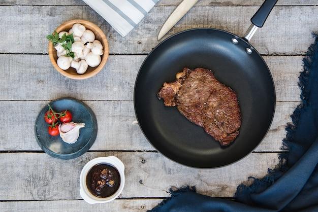 Tir d'un steak grillé dans le stylo et quelques champignons