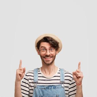 Tir vertical d'un agriculteur joyeux avec une expression heureuse, vêtu d'un pull à rayures décontracté et d'une salopette en denim, pointant vers le haut