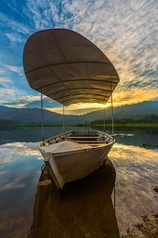 Tir vertical d'un bateau sur un lac au coucher du soleil