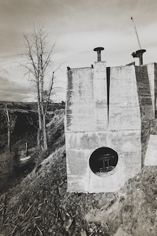 Tir vertical d'un bâtiments sur la colline avec un ciel nuageux en arrière-plan en noir et blanc