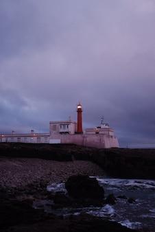Tir vertical d'un beau paysage de phare après le coucher du soleil avec un ciel violet