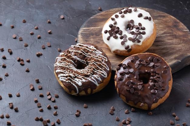 Tir vertical de beignets glacés surmontés de pépites de chocolat sur une surface rustique