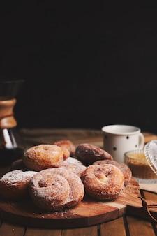 Tir vertical de beignets de serpent avec du sucre en poudre et du café chemex sur une table en bois