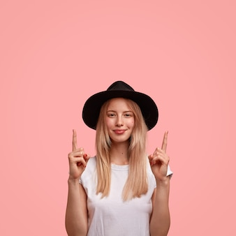 Tir vertical de belle jeune femme aux cheveux longs, vêtue d'un élégant chapeau et gilet, pointe vers le haut avec les deux index
