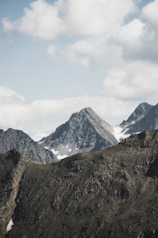 Tir vertical de belles montagnes enneigées sous des nuages à couper le souffle dans le ciel bleu clair