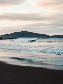 Tir vertical des belles vagues de la mer sur la plage avec les montagnes