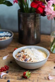 Tir vertical d'un bol de smoothie sain avec des fruits et du granola