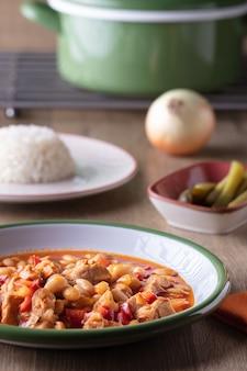 Tir vertical d'un bol de soupe aux légumes, un bol de cornichons et une assiette de riz sur une table en bois