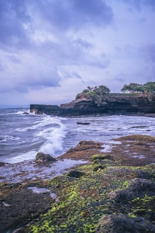 Tir vertical d'un bord de l'océan avec des falaises par temps nuageux