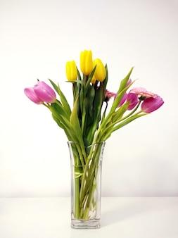 Tir vertical d'un bouquet de tulipes dans un vase sur la table sous les lumières