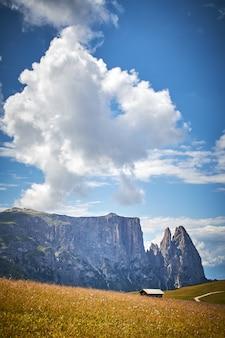 Tir vertical d'une cabine dans un champ herbeux entouré de hautes falaises rocheuses en italie