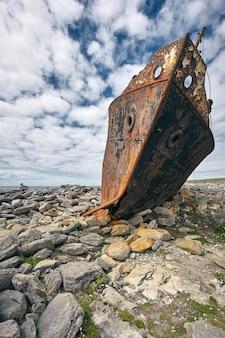 Tir vertical d'une carcasse rouillée du navire plassy dans les îles d'aran, irlande