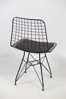 Tir vertical d'une chaise futuriste avec une chaîne à l'arrière derrière un fond blanc