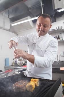 Tir vertical d'un chef masculin gai souriant, salant le boeuf sur un gril