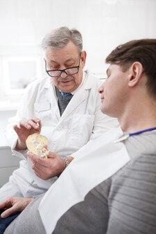 Tir vertical d'un chirurgien-dentiste masculin senior parler à son patient