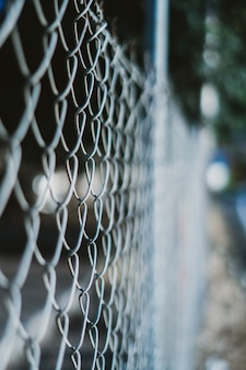 Tir vertical d'une clôture câblée avec un arrière-plan flou
