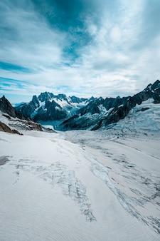 Tir vertical d'une colline enneigée avec des montagnes au loin sous un ciel nuageux