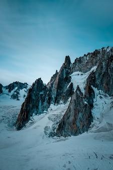 Tir vertical d'une colline enneigée près de la montagne sous un ciel bleu