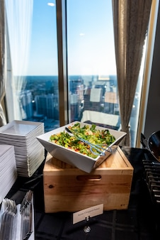Tir vertical d'une délicieuse salade de légumes dans un bol carré
