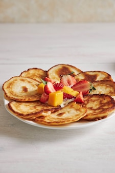 Tir vertical de délicieuses crêpes aux fruits sur table en bois blanc