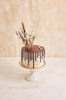 Tir vertical de délicieux gâteau boho avec goutte au chocolat et fleurs sur le dessus avec des décorations dorées