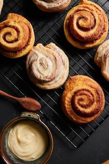 Tir vertical de délicieux petits pains à la cannelle avec un bol en métal de glaçage blanc sur une table noire