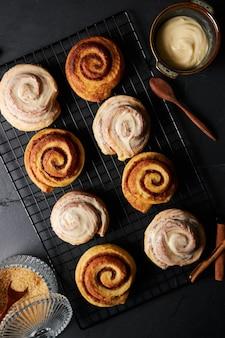 Tir vertical de délicieux petits pains à la cannelle recouverts de glaçage blanc et cuillère en bois sur une table