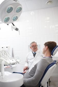 Tir vertical d'un dentiste senior masculin ayant rendez-vous avec le patient à la clinique