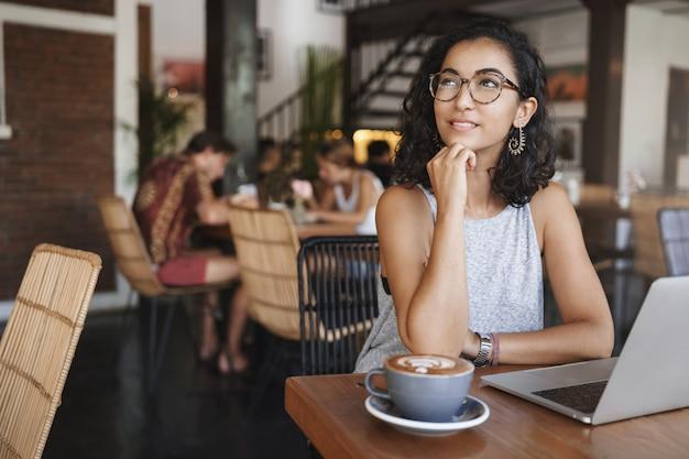 Tir vertical doux tendre femme urbaine détendue portant des lunettes profitant du moment assis seul dans le café