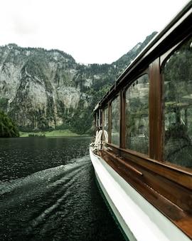Tir vertical du bateau naviguant sur l'eau avec des montagnes boisées au loin