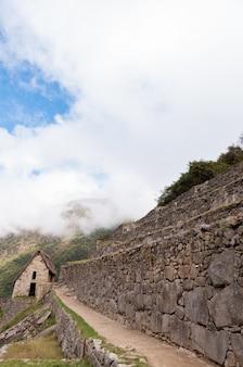 Tir vertical du machu picchu couvert de nuages sur une journée ensoleillée