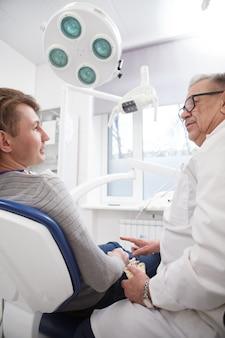 Tir vertical à faible angle d'un homme parlant à son dentiste expérimenté au cabinet dentaire