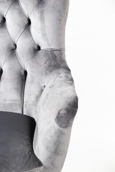 Tir vertical d'un fauteuil gris avec des boutons derrière une surface blanche