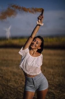 Tir vertical d'une femme de race blanche posant avec une bombe fumigène sur la distance des champs et des moulins à vent
