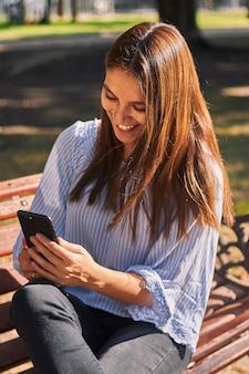 Tir vertical d'une fille assise sur le banc et regardant son téléphone