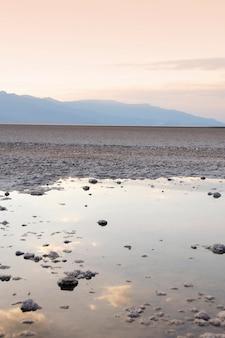 Tir vertical d'une flaque d'eau remplie de beaucoup de roches avec le reflet du coucher de soleil