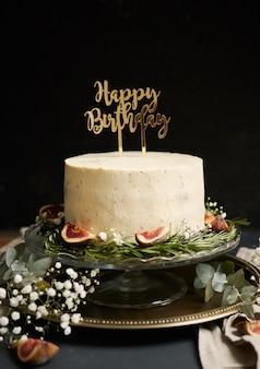 Tir vertical d'un gâteau de rêve blanc joyeux anniversaire avec des feuilles vertes en bas