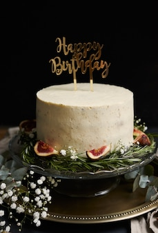 Tir vertical d'un gâteau de rêve joyeux anniversaire avec de la crème blanche sur fond noir
