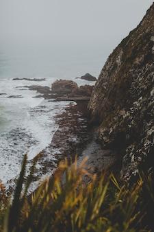 Tir vertical de gros rochers à nugget point ahuriri, nouvelle-zélande avec un fond brumeux