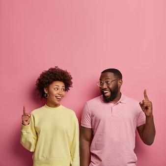 Tir vertical de l'heureux couple à la peau sombre pointer les doigts avant au-dessus sur l'espace vide