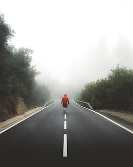 Tir vertical d'un homme marchant sur l'autoroute couverte de brouillard