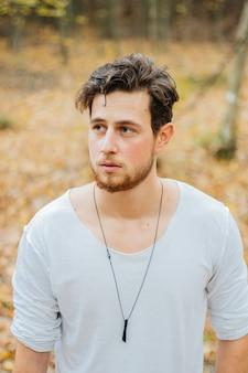 Tir vertical d'un jeune beau mec dans un parc en automne
