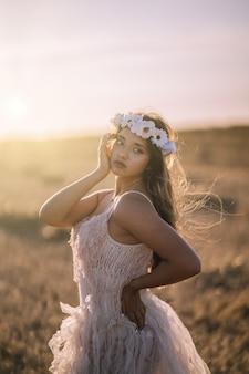 Tir vertical d'une jeune femme de race blanche en robe blanche et couronne de fleurs blanches posant dans un champ