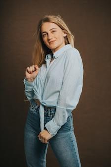 Tir vertical d'une jolie femme blonde en jeans et une chemise courte posant sur un mur marron